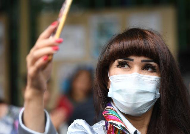 Женщина в таджикском национальном костюме и маске