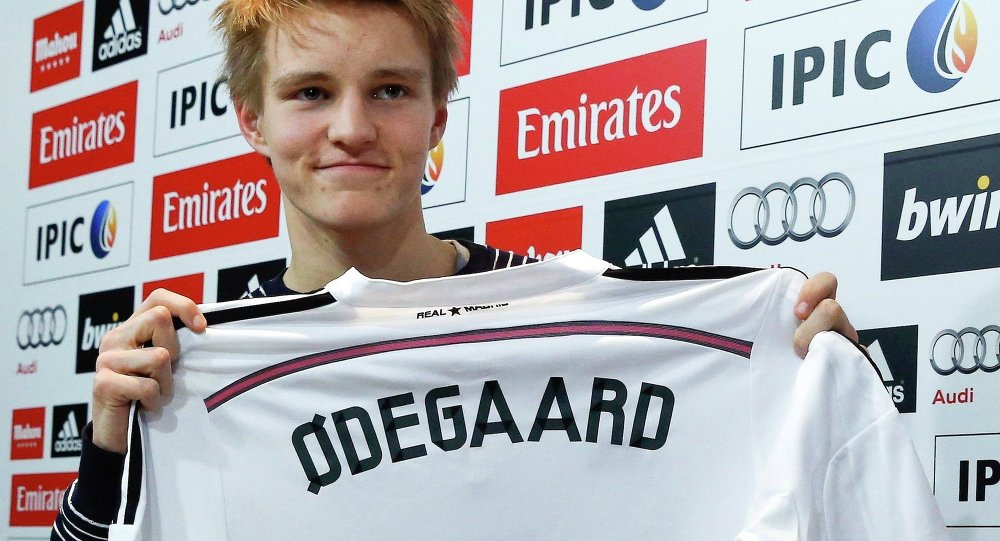 Real Madrid's new teenage signing Martin Odegaard from Norwegian club Stromsgodset holds up his jersey during his presentation at the Valdebebas training grounds in Madrid, January 22, 2015