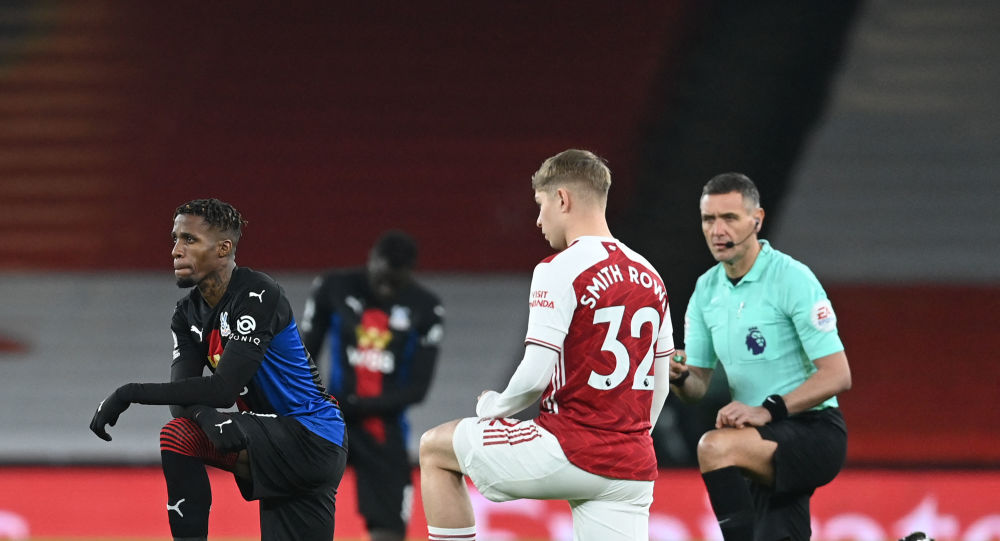 Crystal Palace's Ivorian striker Wilfried Zaha (L), Arsenal's English midfielder Emile Smith Rowe (2nd R) and English referee Andre Marriner (R) 'take a knee' in support of the No Room For Racism campaign