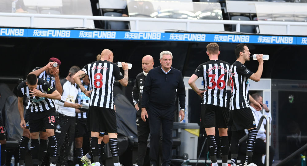 Newcastle United manager Steve Bruce speaks with players during a drink break in a Premier League game with Liverpool.