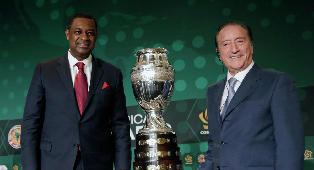 CONCACAF president Jeffrey Webb, left, and Eugenio Figueredo, right, president of CONMEBOL, the South American scoccer Confederation, pose for photographers next to the 2016 Copa America trophy in Bal Harbour, Fla