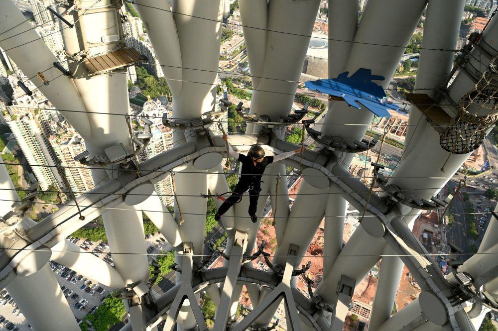 راهنما هنگام راه رفتن روی طناب در پارک Canton در شهر گوانجوی چین