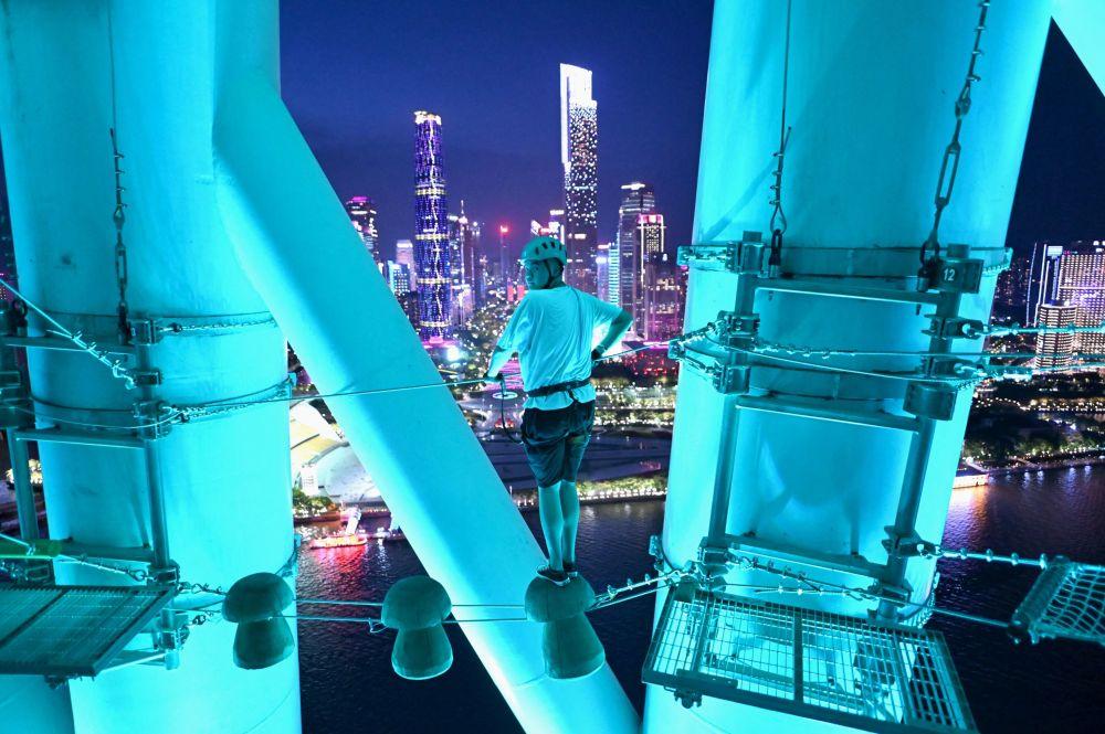 بازدیدکننده هنگام راه رفتن روی طناب در پارک Canton در شهر گوانجوی چین