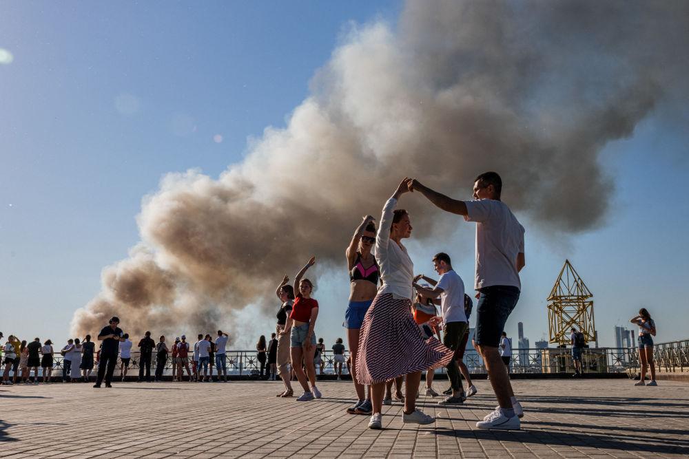 زوج ها همزمان با برخاستن دود از یک انبار تولید مواد شیمیایی در مسکو، سامبا می رقصند.