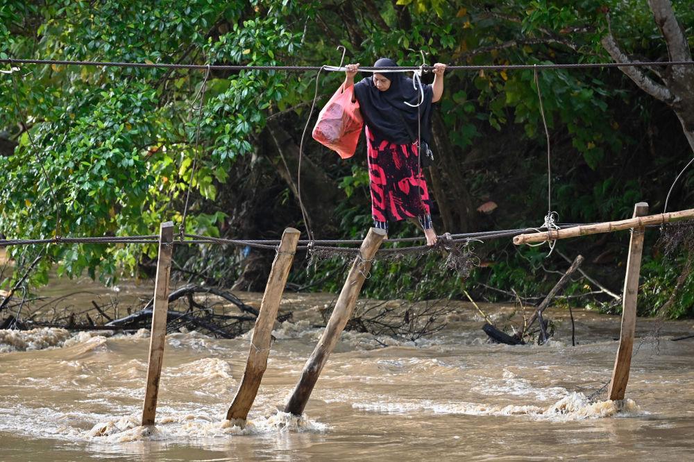 زنی در حال عبور از روی رودخانه در اندونزی