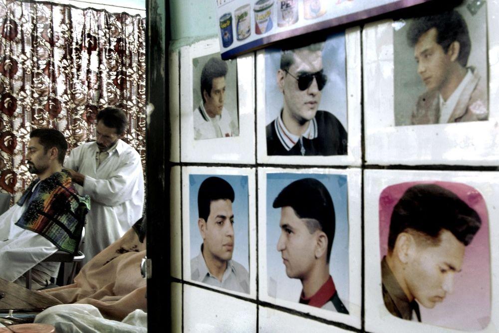 آرایشگاهی در کابل سال 2002، عکس هایی روی دیوار آویزان که سبک های مختلف موها و صورت بدون ریش را نشان می دهد