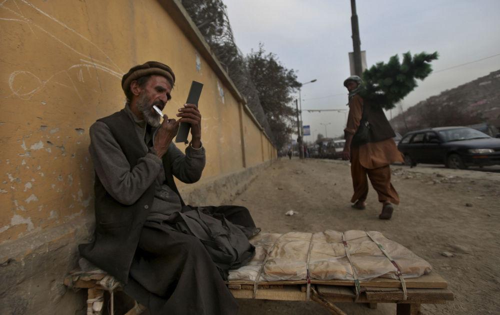 یک آرایشگر خیابانی در کابل سال 2010 در حالی که منتظر مشتری است، ریش خود را اصلاح میکند.