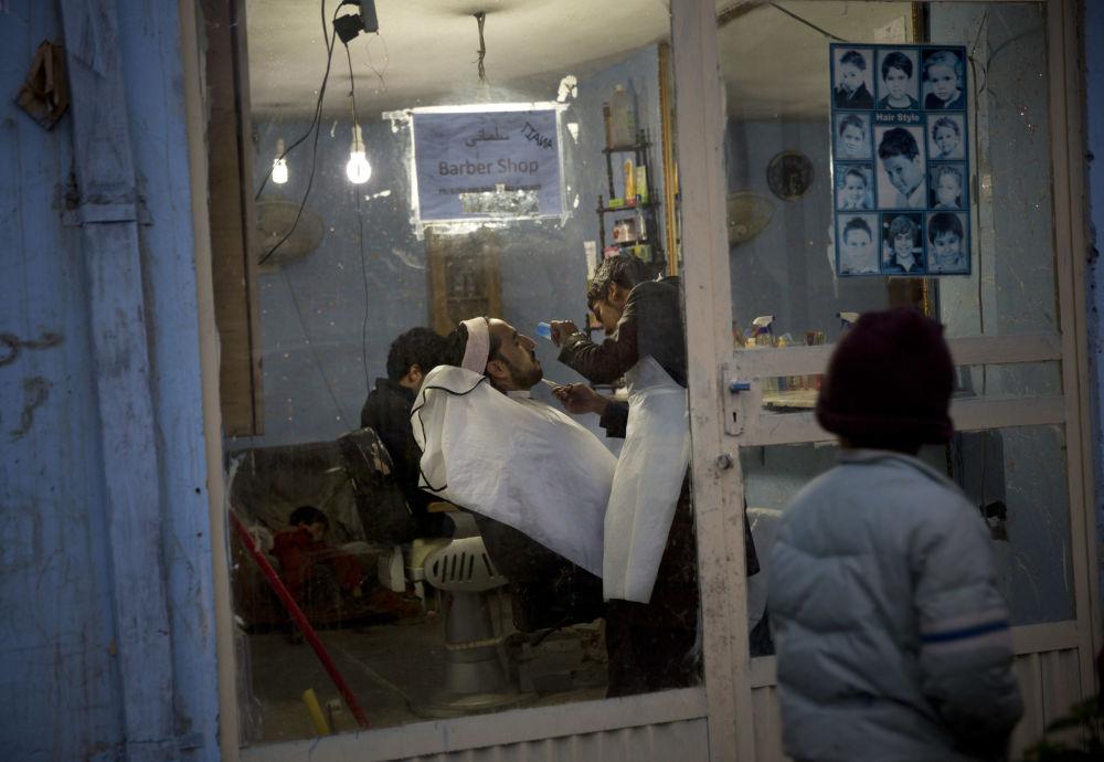 پسری به آرایشگاهی نگاه می کند که در آن ریش مردی را اصلاح میکنند/ کابل - سال 2013.