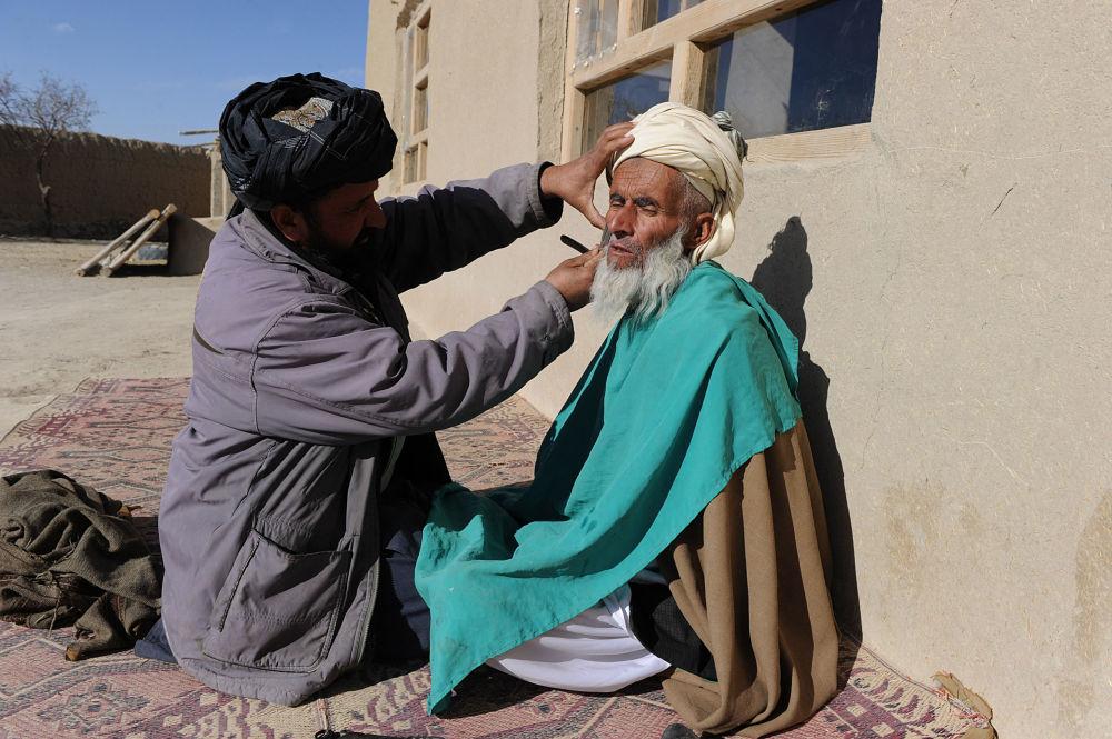 آرایشگر روستایی در حال تراشیدن ریش مردی در ولایت غزنی افغانستان در سال 2011.