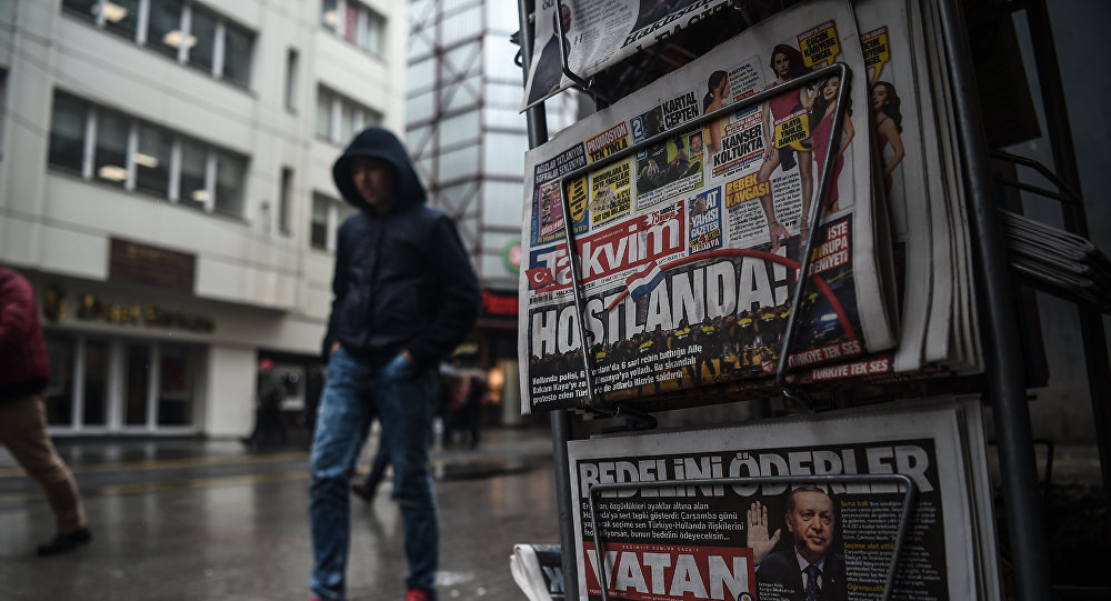 A person walks past a newspaper stand showing their front pages bearing headlines concerning diplomatic tensions between Turkey and The Netherlands, on display in Istanbul on March 13, 2017
