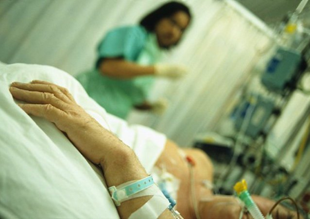 Intensive care. Hand of a patient who is being attended by a nurse in an intensive care unit (ICU)
