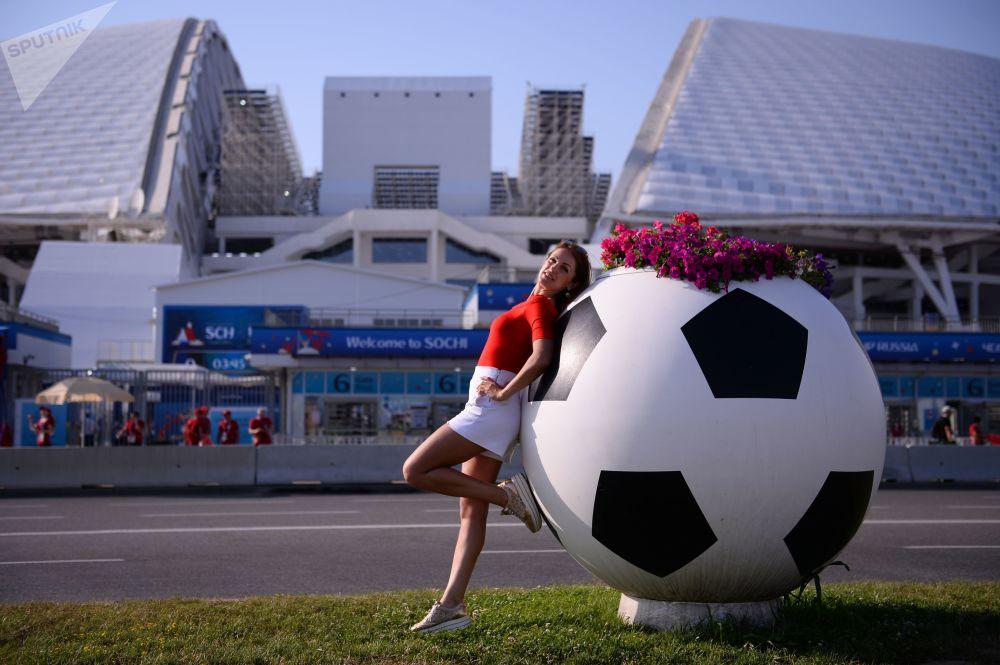 یک هوادار فوتبال در مقابل ورزشگاه المپیک فیشت در حال عکس گرفتن قبل از شروع مسابقه مرحله گروهی جام جهانی میان تیمهای ملی فوتبال پرتغال و اسپانیا