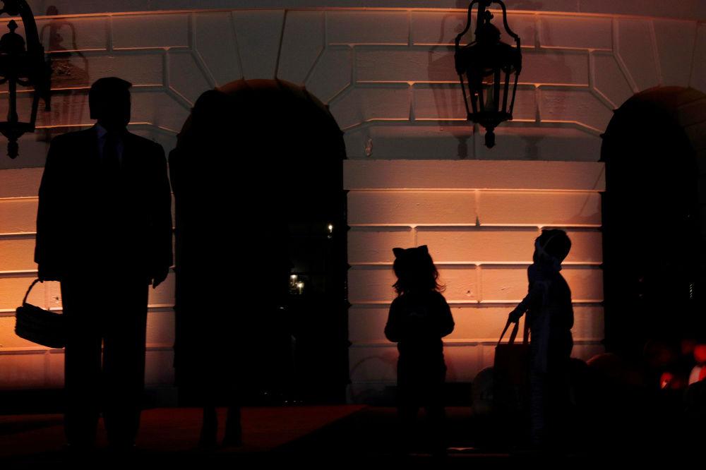 دونالد ترامپ در حال تقسیم شیرینی هالووین به کودکان در کاخ سفید.