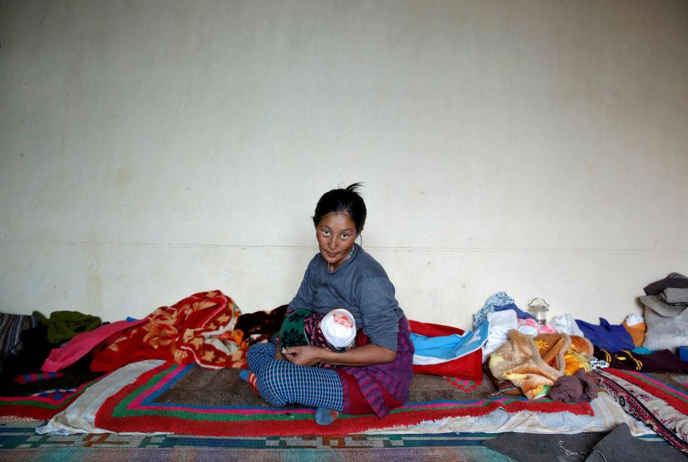 یکی زن روستایی با یک کودک درآغوش به عکاس پوز میگیرد