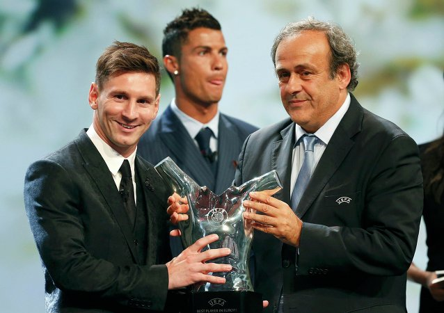 Barcelona's Lionel Messi (L) receives from UEFA President Michel Platini the Best Player UEFA 2015 Award during the draw ceremony for the 2015/2016 Champions League Cup soccer competition at Monaco's Grimaldi Forum while Cristiano Ronaldo (C) looks on in Monte Carlo August 27, 2015